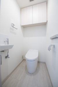 落ち着いたトイレ タンクレストイレで空間をすっきりさせる。収納棚もついているので機能性も高いです。